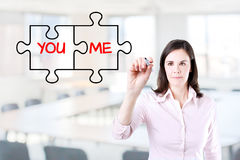Businesswoman drawing a You and Me puzzle love concept on the virtual screen. Office background. Royalty Free Stock Photos