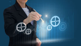 Businesswoman draws gears . Businesswoman draws gears on a blue background Stock Images