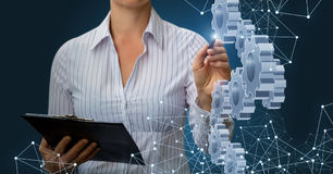 Businesswoman draws a mechanism . Businesswoman draws a mechanism consisting of gears royalty free stock image