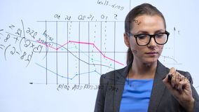 Woman draws various growth charts, calculating prospects for success in a modern glass office stock footage