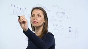 Woman draws various growth charts, calculating prospects for success in a modern glass office. Businesswoman draws various growth charts, calculating prospects stock video footage