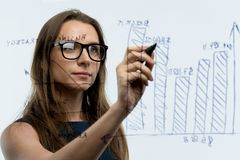 Woman draws various growth charts, calculating prospects for success in a modern glass office. Businesswoman draws various growth charts, calculating prospects stock photography