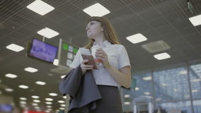 Businesswoman drink coffee in the airport hall. Handsome businesswoman wearing costume is in the airport hall. Handsome lady drinks her drink, holds her passport stock video