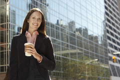 Businesswoman With Drink Outside Office Building Royalty Free Stock Photography