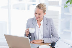 Businesswoman drinking coffee behind her computer Royalty Free Stock Images