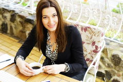 Businesswoman drinking coffee in a cafe. Attractive smiling adult businesswoman drinking coffee in a cafe Stock Photography