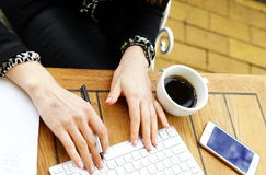 Businesswoman drinking coffee in a cafe. Business woman`s hands typing on laptop keyboard Stock Photography