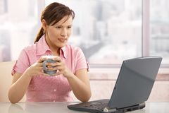 Businesswoman drinking coffee at desk Stock Photo