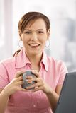 Businesswoman drinking coffee at desk Stock Photos