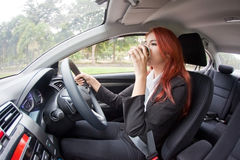 Businesswoman drinking coffee while driving Stock Photos