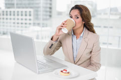 Businesswoman drinking coffee at her desk in front of laptop Stock Images