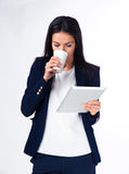 Businesswoman drinking coffee and holding tablet computer Stock Photography