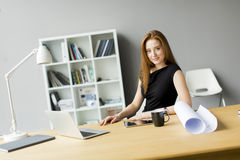 Businesswoman drinking coffee in office Royalty Free Stock Images
