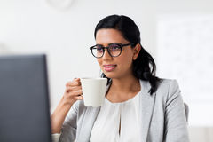 Businesswoman drinking coffee at office computer Stock Images