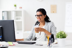 Businesswoman drinking coffee at office computer royalty free stock image