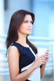 Businesswoman drinking coffee outdoors Stock Images