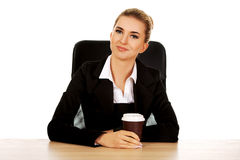 Businesswoman drinking coffee from paper cup behind the desk Royalty Free Stock Photography