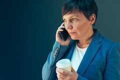 Businesswoman drinking coffee to go and talking on mobile Royalty Free Stock Image
