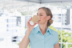 Businesswoman drinking from disposable coffee cup Stock Photography
