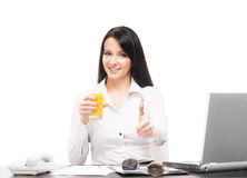 A businesswoman drinking orange juice in an office Stock Image