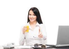 A businesswoman drinking orange juice in an office Stock Image