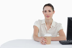 Businesswoman drinking a takeaway coffee while using a computer Stock Photos