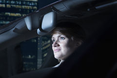 Businesswoman driving at night in the city Stock Images