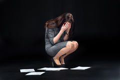 Businesswoman with dropped documents. Depressed young businesswoman crying over dropped documents stock images