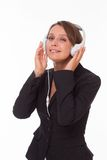 Businesswoman with earphones on white Royalty Free Stock Photos