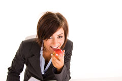 Businesswoman eating apple. A young business woman eating an apple, on white studio background Royalty Free Stock Photography