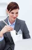 Businesswoman eating chinese food with chopstick Stock Images