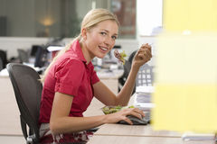 Businesswoman eating at desk in office, smiling, portrait royalty free stock photography