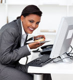 Businesswoman eating an eclair at work Stock Photography