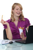 Businesswoman eating fries Stock Photo