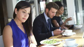 Businesswoman Eating Lunch And Reading Newspaper In Café. Line of business people sitting in window of café using digital devices and eating lunch.Shot stock footage