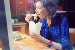 Free Businesswoman Eating Noodles At Desk Royalty Free Stock Images - 82135439