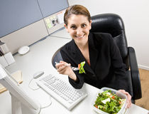 Businesswoman eating salad at desk Royalty Free Stock Photos