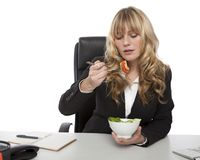 Businesswoman eating salad at her desk Stock Photo