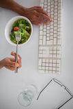 Businesswoman eating a salad at her desk Stock Photos