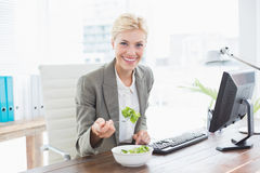 Businesswoman eating salad on her desk Stock Photography