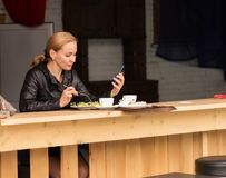Lunch in an outdoor cafe. businesswoman eating salad and checks email on your phone Royalty Free Stock Photography