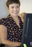 Businesswoman eating sandwich at desk, using computer, smiling Royalty Free Stock Image