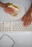 Businesswoman eating a sandwich at her desk Stock Photo