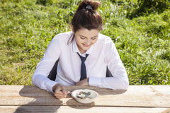 Businesswoman eats breakfast in the open air, money in a plate Royalty Free Stock Photos