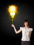 Businesswoman with an eco-friendly  bulb. Businesswoman hold a shining eco-friendly idea bulb on a black background Stock Photo