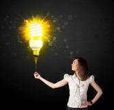Businesswoman with an eco-friendly  bulb. Businesswoman hold a shining eco-friendly idea bulb on a black background Royalty Free Stock Photography
