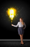 Businesswoman with an eco-friendly  bulb. Businesswoman hold a shining eco-friendly idea bulb on a black background Stock Photography