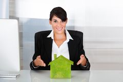 Businesswoman With Eco House. Happy Businesswoman Holding Green Eco House At Desk Royalty Free Stock Photography