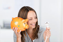 Businesswoman With Electric Plug And Piggy Bank. Portrait of happy mid adult businesswoman with electric plug and piggy bank in office stock photos