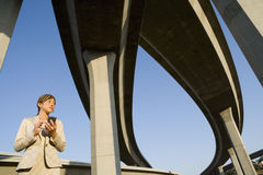 Businesswoman with electronic organiser beneath overpasses, low angle view Stock Images